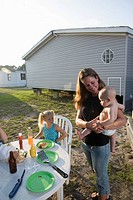 Young woman with children in backyard outside trailer home