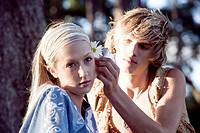 View of a young couple in vintage 1960´s hippie, putting flower behind ear