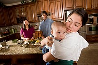 Girl holding baby while mom prepares dinner in background