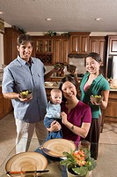 Portrait of an Asian_Caucasian family holding up bowls of food at a dining table