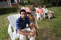 Portrait of interracial couple sitting together with parents background