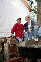 Mature couple conversing next to stack of bricks outside house