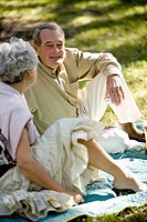 Mature couple sitting on a picnic blanket