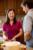 Caucasian man conversing with Asian woman while she prepares food in the kitchen