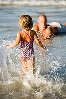 Little girl splashing in water while father watches at the beach