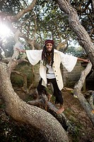 Portrait of a smiling pirate standing on a tree trunk