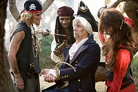 View of armed pirates holding a navy officer captive and threatening him with a sword and a gun