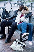 Contemplative young inter_racial couple embracing on a park bench