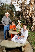 Portrait of a cheerful Tex_Mex family sitting together in the backyard of house