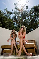 Two young women in bikinis sitting in shade on deck chairs