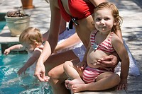 Mothers and baby daughters at swimming pool