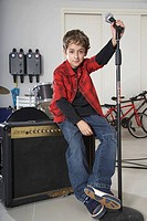 Boy 10-11 sitting on amplifier, holding microphone, portrait