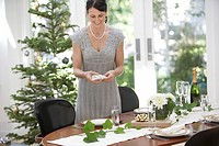 Mature woman setting dinner table for Christmas dinner