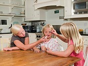 Sisters 8-11 putting play make-up on younger girl 8-9, sitting at kitchen table