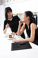 Two business woman sharing slice of cake in work kitchen