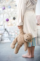 Girl 8-9 holding teddy bear, in front of Christmas tree, low section