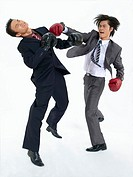 Two businessmen wearing boxing gloves fighting in studio