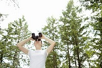 Woman standing in forest looking through binoculars, low angle view