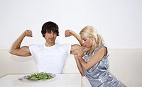Young man sitting on front of spinach, flexing muscles, woman touching bicep