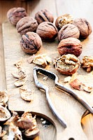 Wet walnuts on chopping board with nut cracker