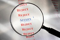 Accept´ sign in list of rejections viewed through magnifying glass, close-up