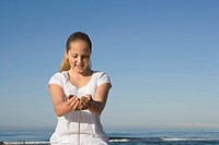 Preteen girl holding sand in hands