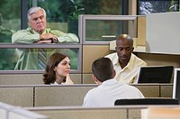 Businessman watching businesspeople in cubicles