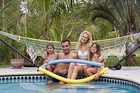 Smiling family relaxing at swimming pool