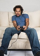 Young man sitting on sofa and playing video game