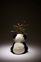 Bamboo leaf on toy panda bear, rear view, studio shot