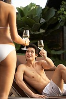 Young couple in swimwear drinking wine outdoors