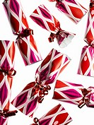 Several red and pink party crackers on white background