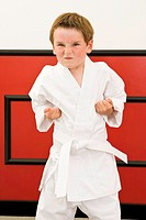 Boy 4-5 years standing in karate pose, portrait