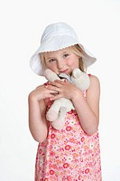 Portrait of a blond girl with a hat and toy animal (thumbnail)