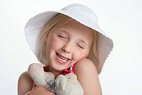 Portrait of a blond girl with a hat and toy animal