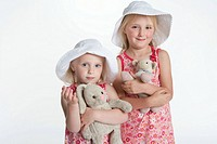 Portrait of two blond girls with hats and their toy animal