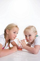 Two blond girls drinking lemonade with a straw