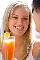 Young woman by cocktail, smiling at friend, close-up