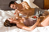Young man holding strawberry above woman´s mouth in bedroom