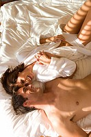 Young couple lying on bed together, elevated view