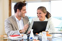 Couple with laptop in sushi bar, smiling at each other