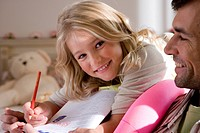 Girl 6-8 doing homework by father, smiling, portrait