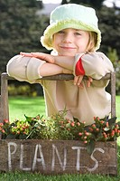 Girl 5-7 wearing hat leaning on handle of plant box, smiling, portrait