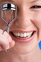 Young woman using eyelash curler, smiling, close-up