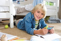 Boy 6-8 with packet of marker pens in bedroom, smiling, portrait