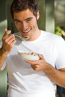 Young man eating breakfast, smiling, portrait