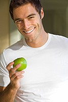 Young man with apple, smiling, portrait, close-up