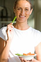 Woman with bowl of vegetable sticks, smiling, portrait (thumbnail)