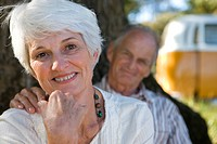 Portrait of senior couple, man's hand on woman's shoulder, smiling focus on woman (thumbnail)