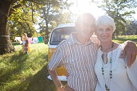 Senior couple arm in arm by camper van, smiling, portrait lens flare